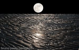 paesaggio onirico luna in cielo nero su terra con acqua che si ritira