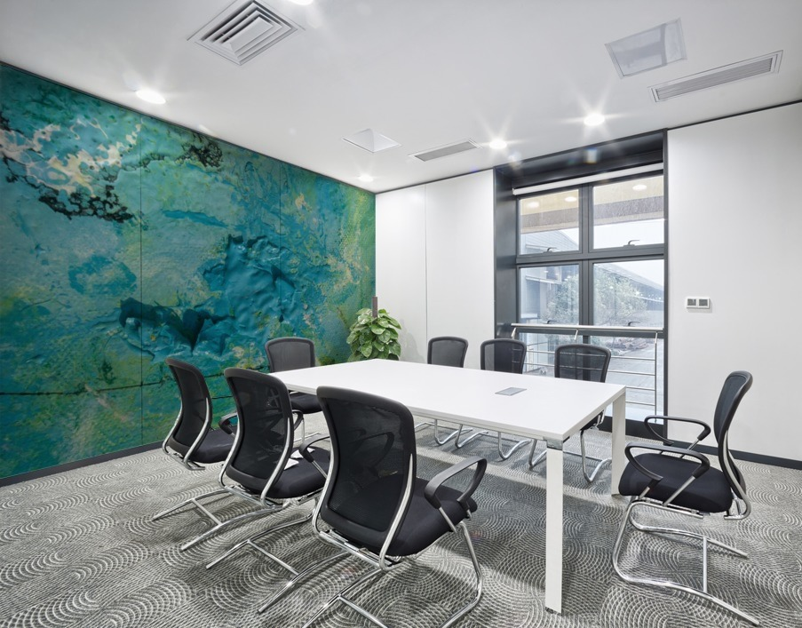 stampa murale adesiva astratta con tema che richiama un blue hole con striature gialle ambientata in una sala riunioni