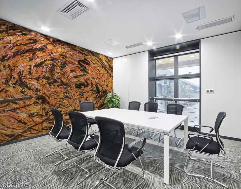 adesivo murale con un tema autunnale astratto rappresentato da un vortice di foglie e alberi con dominante di colore marrone sulla parete di una sala riunioni