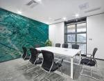 stampa murale astratta con striature di luci,linee e onde di colore verde chiaro e blu su parete di sala riunioni